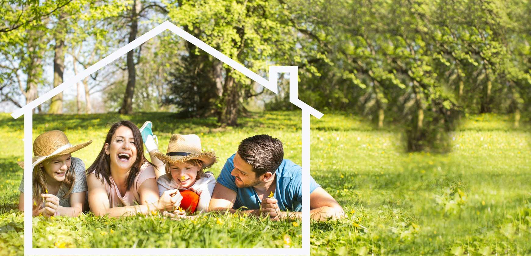 Familie auf Wiese mit weißem Hausumriss rundherum
