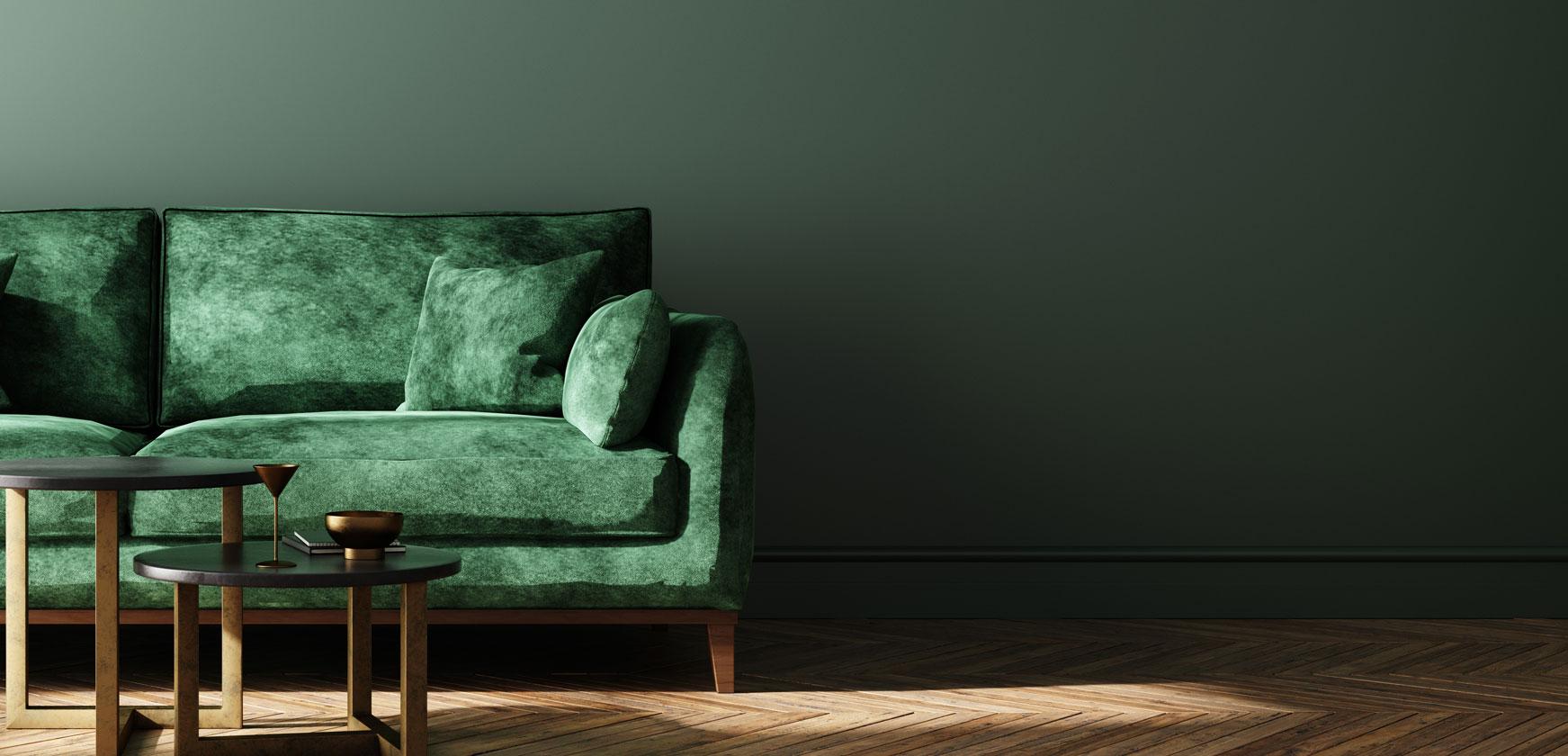 Designerfoto von einer gruenen Samtcouch vor dunkelgruenem Hintergrund auf Parkettboden
