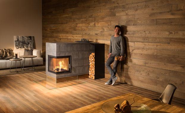 Mann steht neben einem Kachelofen vor einer Holzwand und tut so, als würde er sich wohlfühlen.